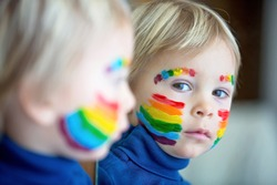 Beautiful blond toddler boy with rainbow painted on his face and messy hands, smiling happily