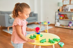 Beautiful blond toddler girl playing with plastic frogs toys at kindergarten