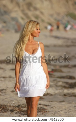 Beautiful Blond walking on the beach at Sunset in a White dress.
