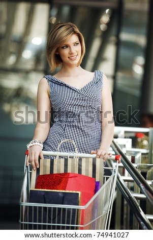 Beautiful blond with shopping cart near supermarket