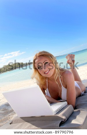 Beautiful blond woman at the beach with laptop computer
