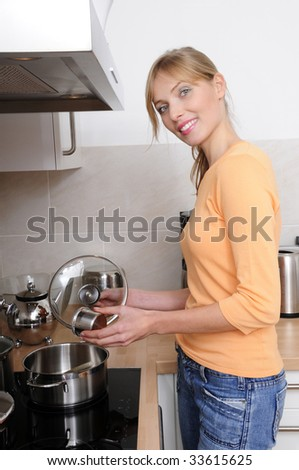 beautiful blond woman cooking a tasty meal in a modern kitchen