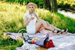 Beautiful blond woman enjoying a pick nick outdoors. Pick nick for one.