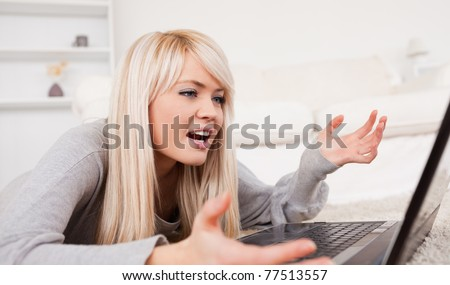 Beautiful blond woman frustrated with her computer lying on a carpet in the living room