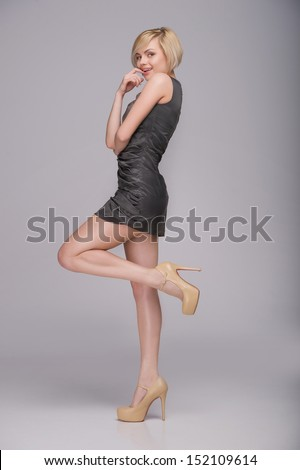 Beautiful blond woman. Full length of beautiful young woman posing and smiling while standing isolated on grey