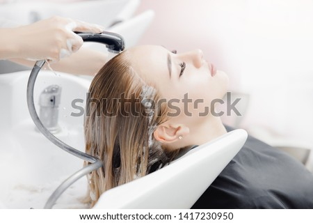 Beautiful blond woman getting hair wash in beauty salon. Concept head treatment care.