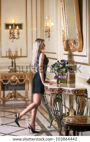 Beautiful blond woman in lacy dress looking in the mirror in luxury interior
