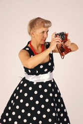 Beautiful blond woman in pinup style, dressed in a polka-dot dress, stands and holds a camera in front of her, looking in the wrong viewfinder, does not know how, is trained, white background.