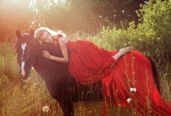 beautiful blond woman in red dress at black horse