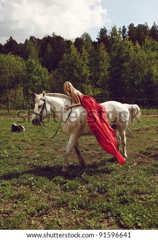 Beautiful blond woman in red dress on a white horse