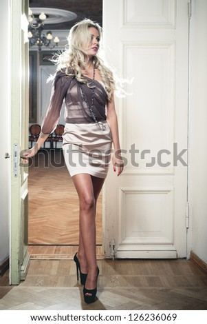 Beautiful blond woman in vintage interior - stock photo
