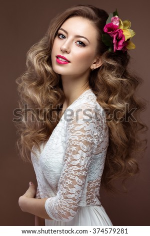 Beautiful blond woman in wedding dress with evening make-up, tender lips and curls. Bride image. Beauty face. Picture taken in the studio on a gray background