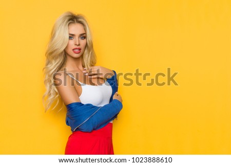 Beautiful blond woman in white tank top and blue jacket is posing with hand on chest and looking at camera. Three quarter length studio shot on yellow background.