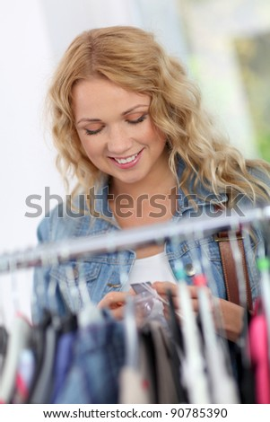 Beautiful blond woman looking at price tags in store