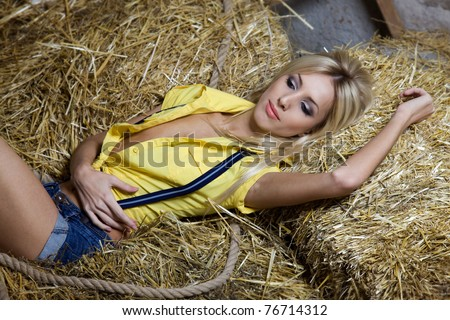 Beautiful blond woman lying down on haystack