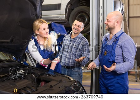 Beautiful blond woman mechanic in workwear repairing a car with a wrench while her colleague and driver offer her their help