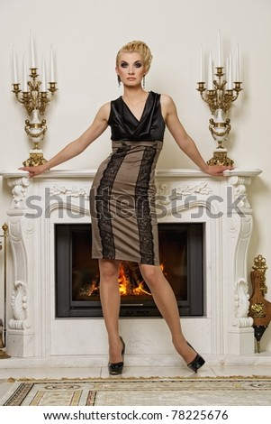 Beautiful blond woman near the fireplace in a luxury interior
