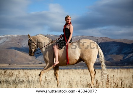 stock photo : Beautiful blond woman riding an Arabian horse.