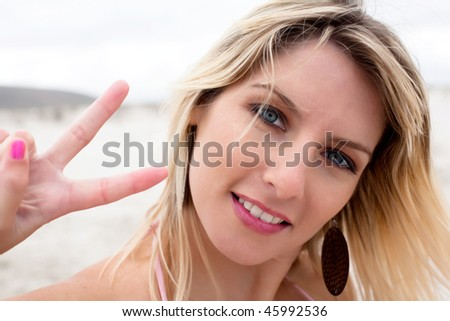 Beautiful blond woman showing a peace sign with her right hand.