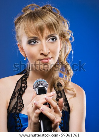 beautiful blond woman singing on a microphone on blue background