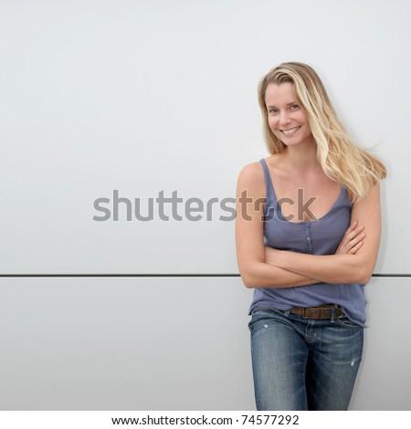 Beautiful blond woman standing on grey background
