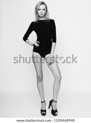 Stock Photo Beautiful blond woman wearing black fashionable lingerie, studio shot over white background
