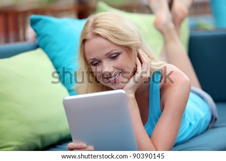 Beautiful blond woman websurfing with electronic tablet