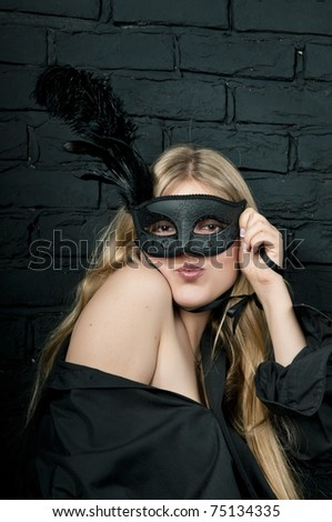 Beautiful blond woman with black carnival mask - stock photo