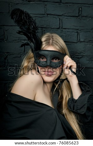 Beautiful blond woman with black carnival mask