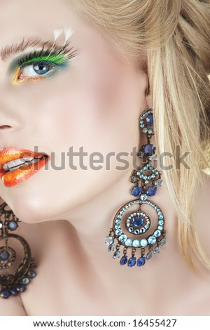 Beautiful blond woman with bright orange lips and false feather lashes in diamante chandelier earrings