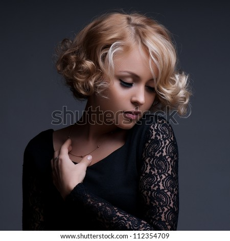 Beautiful blond woman with elegant black dress. Fashion photo