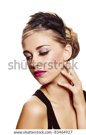 Beautiful blond woman with fashion make-up wearing hair in a classic french roll updo hairstyle with feather band over white studio background .