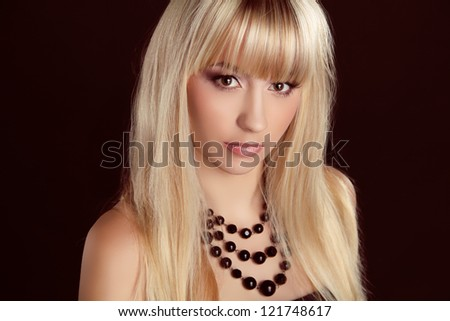 Beautiful blond woman with long hair styling isolated on black background. Fashion and Jewelry