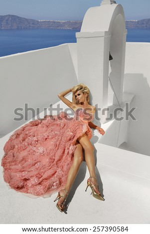 Beautiful blond woman with long legs lying on the background of a beautiful view of the sea in a fantastic pink dress in Santorini