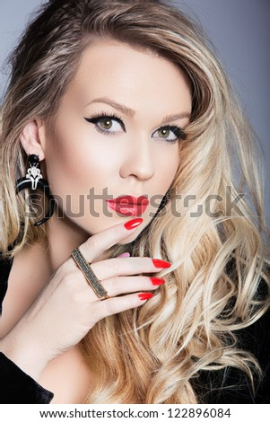 Beautiful blond woman with red nail polish manicure and cat eye makeup wearing long curly hairstyle