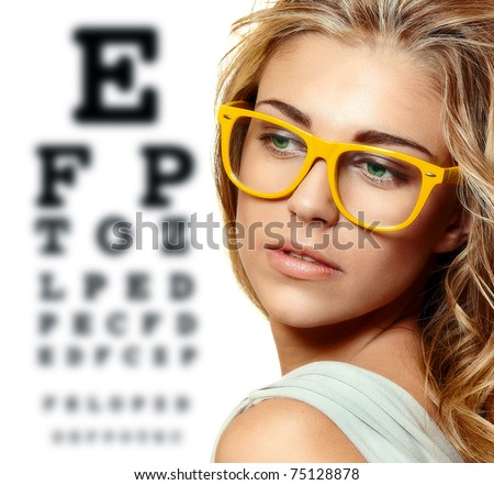 beautiful blond woman with yellow trendy glasses on the background of eye test chart
