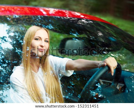 Beautiful blond young woman driving a sports car
