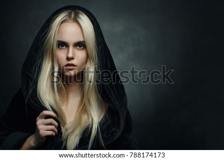 Stock Photo beautiful blond young woman in black hood looking at camera