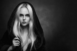beautiful blond young woman in black hood looking at camera, monochrome