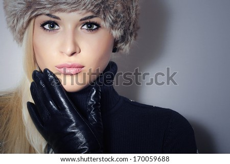 Beautiful Blond Young Woman In Fur Hat. Beauty Girl In Black Leather Gloves. Winter Fashion. Pretty Model