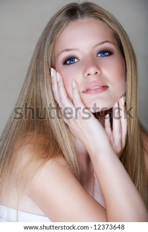 Beautiful blond young woman in her 20s with soft smile and hands around her face