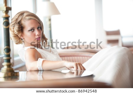 beautiful blond young woman in wedding dress seated, posing looking at the camera. Professionally done hair and makeup.