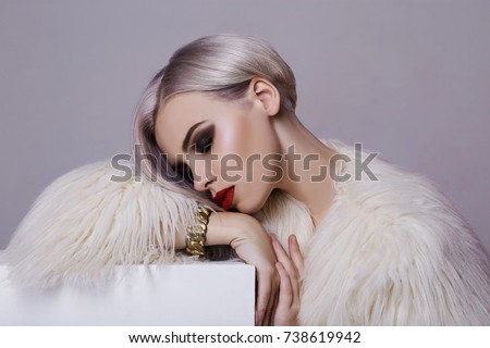 Beautiful blond young woman in white fur.winter fashion.Beauty sexy Model Girl with bob hair and make-up