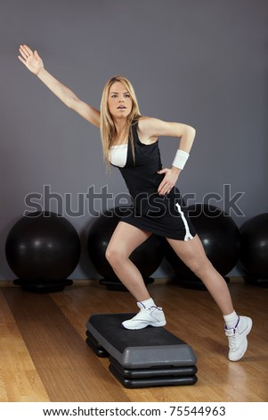 Beautiful blond young woman performing step aerobics exercise in a gym