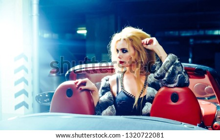 beautiful blond young woman posing inside cabriolet car in dark underground parking space. Cute girl poising between orange leather seat. Big metal fashion chain on brest stock photo