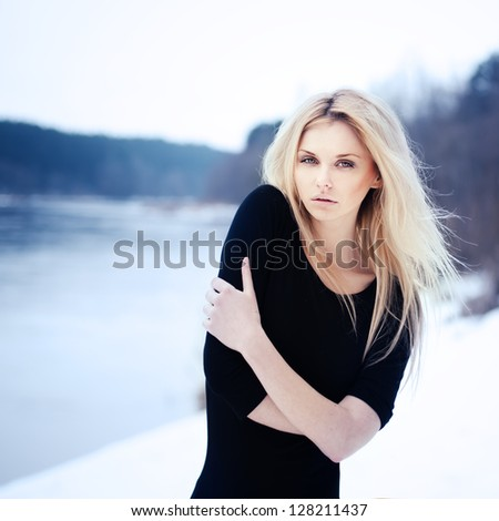 beautiful blonde at the river freezes. Photo in cold tones - stock photo