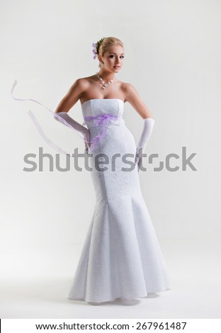 Beautiful blonde bride in wedding dress with flowing ribbons on white background in Studio