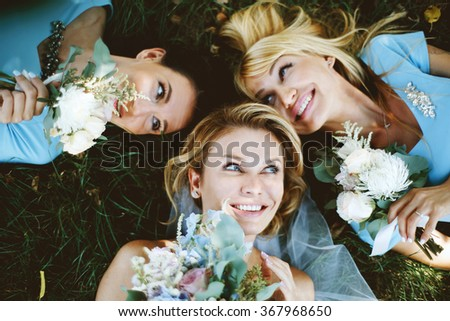 Beautiful blonde bride lying on the grass and smiling with her bridesmaids in blue summer dress in the park on her happy  wedding day