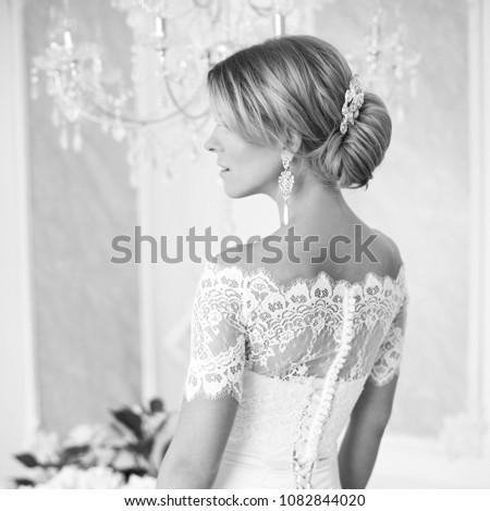 Beautiful blonde bride posing in white elegant dress in bright luxury interior #1082844020
