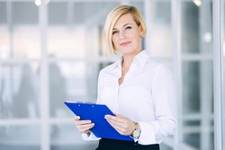 Beautiful blonde business woman in a white shirt with a folder of documents in an office building.